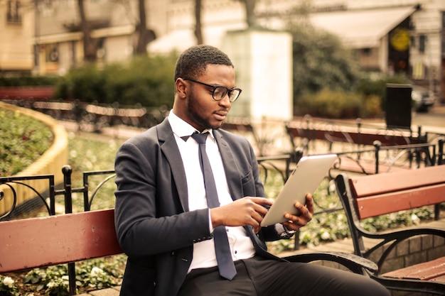 Bel homme d'affaires afro à l'aide d'une tablette