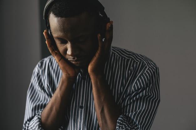 Bel homme d'affaires afro-américain dans des vêtements décontractés et des écouteurs écoute de la musique à l'aide d'un téléphone intelligent