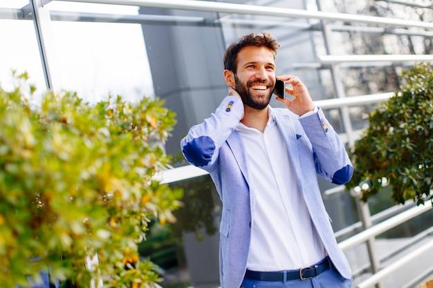 Bel homme d'affaires à l'aide de téléphone portable en face de l'immeuble de bureaux