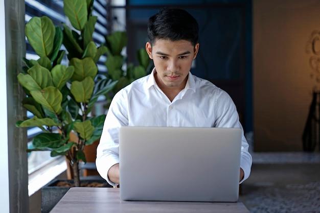 Bel homme d'affaires asiatique ou employé de bureau travaillant au café
