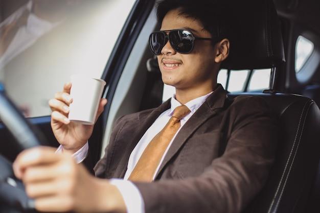 Un bel homme d'affaires asiatique à lunettes de soleil conduit une voiture tout en tenant une tasse de café