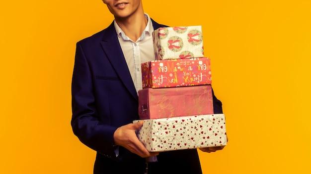 Bel homme d'affaires asiatique tenant une boîte-cadeau sur fond jaune