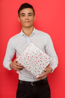 Bel homme d'affaires asiatique tenant une boîte-cadeau sur fond rouge