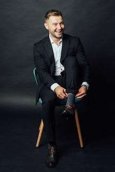 Bel homme d'affaires assis sur une chaise en studio photo