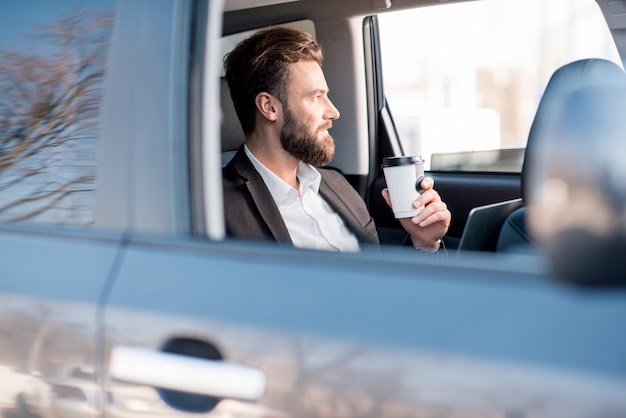 Bel homme d'affaires assis avec du café pour aller sur la banquette arrière de la voiture