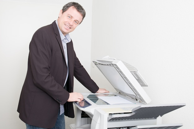 Bel homme d'affaires au lieu de travail avec copieur de machine à copier au bureau