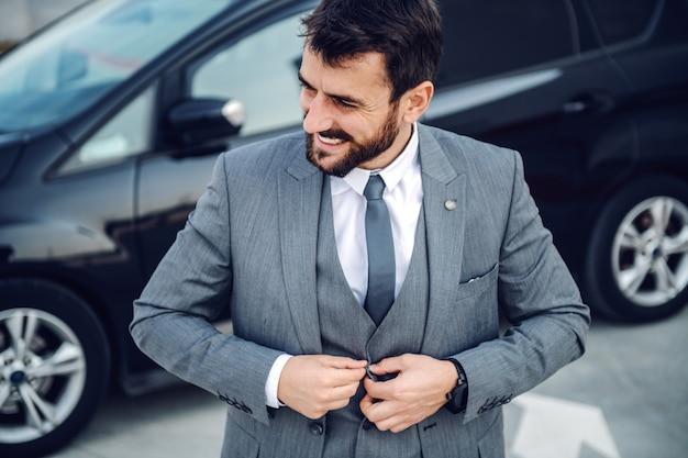 Bel homme d'affaires barbu caucasien souriant debout à l'extérieur et boutonnant son gilet. en arrière-plan, sa voiture.