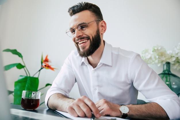 Bel homme d'affaires barbu dans des verres et une chemise blanche travaille sur l'ordinateur portable et a une conversation web en ligne avec son équipe.