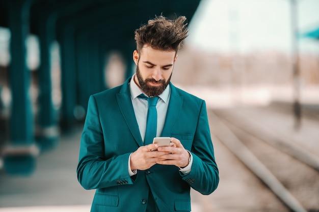 Bel homme d'affaires barbu du caucase en costume turquoise à l'aide de téléphone intelligent en attendant l'arrivée du train. les opportunités ne se produisent pas simplement, vous les créez.