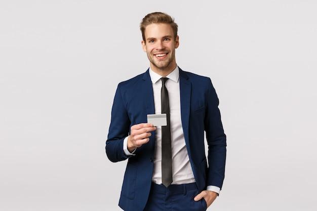 Bel homme d'affaires blond élégant et réussi en costume classique, tenant une carte de crédit et souriant sûr de lui, la main dans un pantalon de poche, promouvoir le système bancaire, faire un achat, fond blanc debout