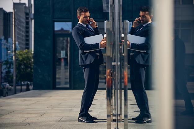 Bel homme d'affaires brune tenant du café dans ses mains et parlant au téléphone tout en ouvrant la porte