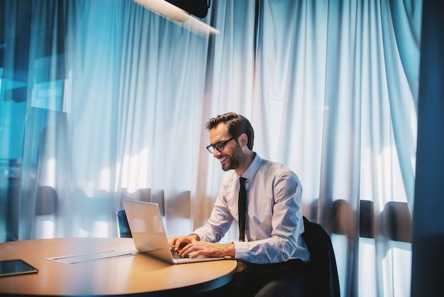 Bel homme d'affaires caucasien heureux en chemise et cravate et avec des lunettes assis au bureau et travaillant sur un projet important. concept d'entreprise.