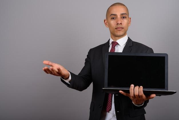 Bel homme d'affaires chauve portant costume avec ordinateur portable sur fond gris