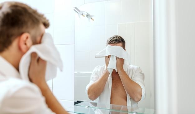 Bel homme d'affaires avec une chemise déboutonnée essuyant son visage avec une serviette tout en se tenant dans la salle de bains de l'auberge devant le miroir.