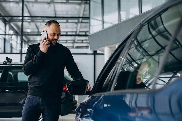 Bel homme d'affaires choisissant une voiture dans une salle d'exposition de voiture