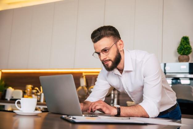 Bel homme d'affaires confiant dans des vêtements décontractés intelligents travaille avec un ordinateur portable à la cuisine domestique
