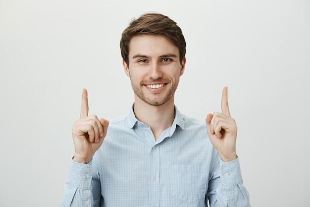 Bel homme d'affaires confiant pointant les doigts vers le haut