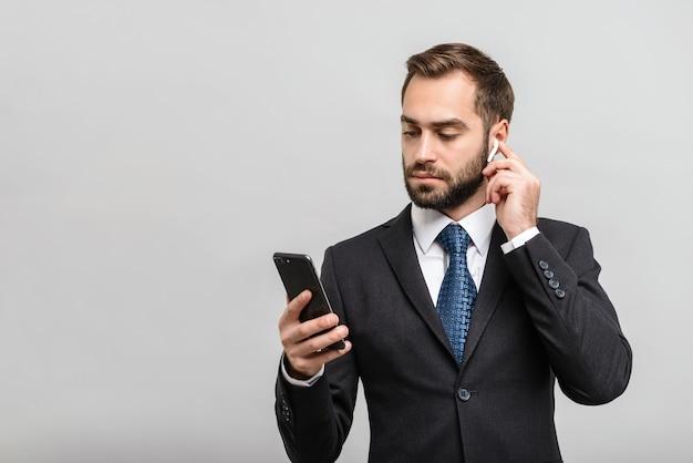 Bel homme d'affaires confiant portant un costume debout isolé sur un mur gris, écoutant de la musique avec des écouteurs et un téléphone portable