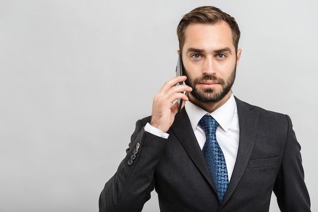Bel homme d'affaires confiant portant un costume debout isolé sur un mur gris, parlant au téléphone mobile