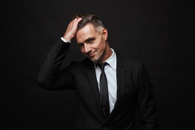 Bel homme d'affaires confiant portant un costume debout isolé sur un mur noir, posant