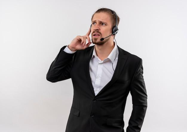 Bel homme d'affaires en costume et casque avec un microphone à l'écoute d'un client à la confusion debout sur fond blanc