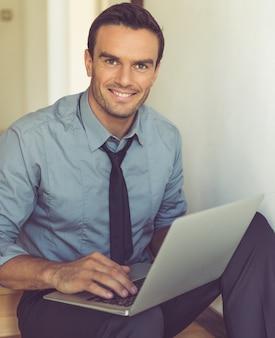Bel homme d'affaires en costume classique utilise un ordinateur portable