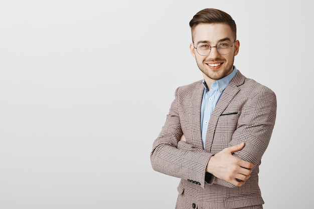 Bel homme d'affaires en costume et lunettes croise la poitrine des bras et regarde