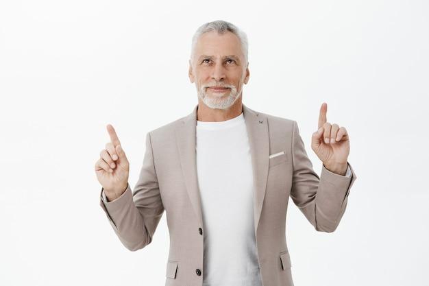 Bel homme d'affaires en costume pointant les doigts vers le haut et souriant heureux