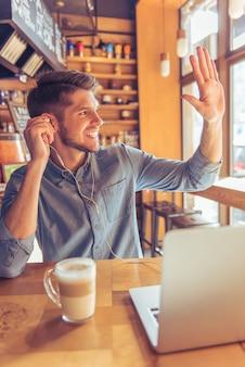 Bel homme d'affaires dans les écouteurs utilise un ordinateur portable.