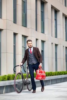 Bel homme d'affaires dans une veste et un sac rouge et son vélo dans les rues de la ville.