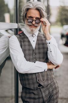 Bel homme d'affaires debout à l'extérieur et penser