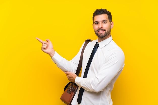 Bel homme d'affaires sur un doigt pointé de mur jaune isolé sur le côté