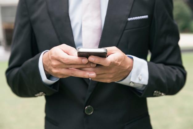 Bel homme d'affaires écrivant un e-mail ou un message au téléphone