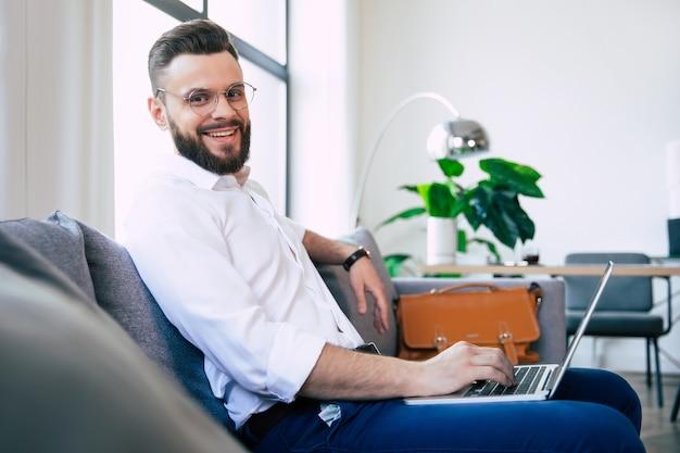 Bel homme d'affaires élégant barbu pendant qu'il travaille dans l'ordinateur portable et assis sur le canapé