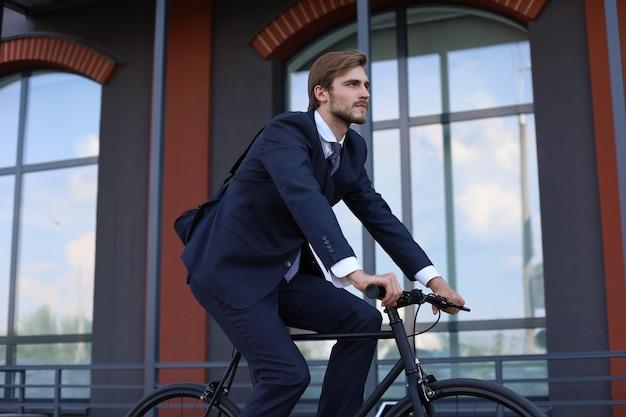 Bel homme d'affaires faisant du vélo pour travailler dans la rue urbaine le matin.