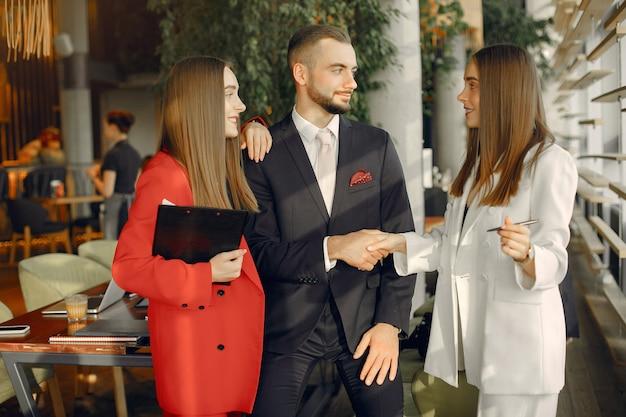 Bel homme d'affaires avec des femmes debout et travaillant dans un café