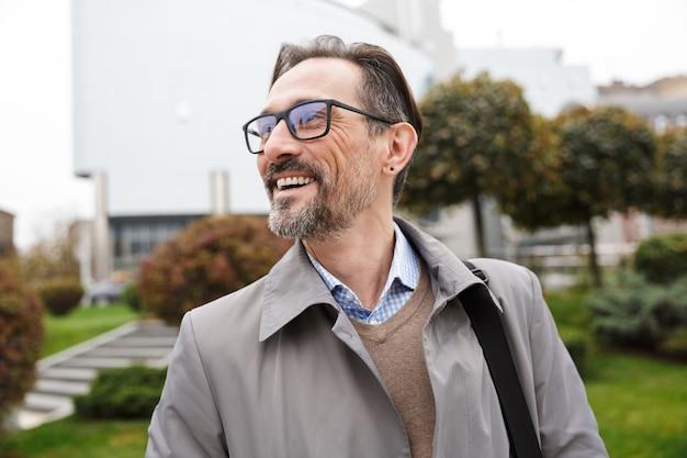 Bel homme d'affaires gai à lunettes regardant de côté et riant en marchant dans la rue de la ville