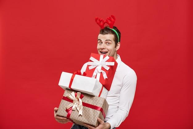Bel homme d'affaires heureux caucasien tenant beaucoup de cadeaux avec bonnet de noel posant sur fond isolé blanc.