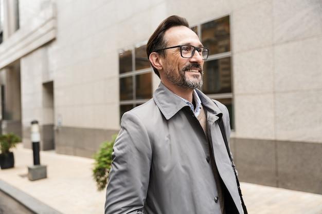 Bel homme d'affaires joyeux à lunettes souriant en marchant près d'un immeuble de bureaux