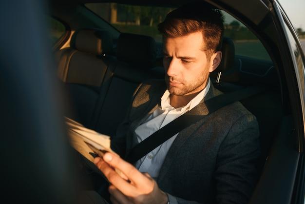 Bel homme d'affaires lisant le journal alors qu'il était assis