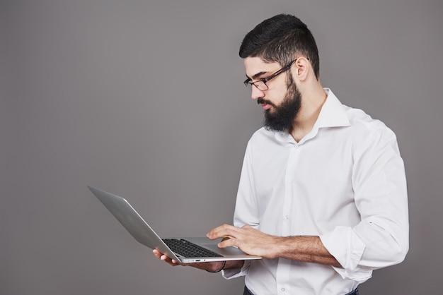 Bel homme d'affaires à lunettes et costume tenant un ordinateur portable dans les mains et écrire quelque chose.