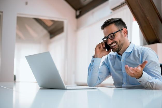 Bel homme d'affaires à lunettes utilise un ordinateur, parler au téléphone mobile.