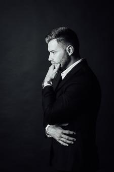 Bel homme d'affaires masculin avec costume posant dans un studio photo. portrait demi-longueur