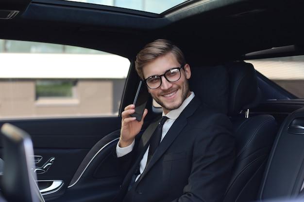 Bel homme d'affaires parlant avec téléphone assis avec ordinateur portable sur la banquette arrière de la voiture.