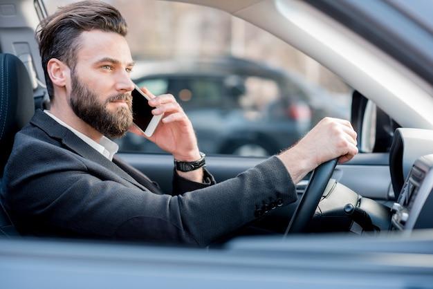 Bel homme d'affaires parlant avec un téléphone en conduisant une voiture dans la ville