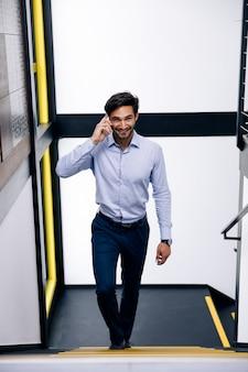 Bel homme d'affaires, parler au téléphone mobile et monter les escaliers dans le bureau moderne