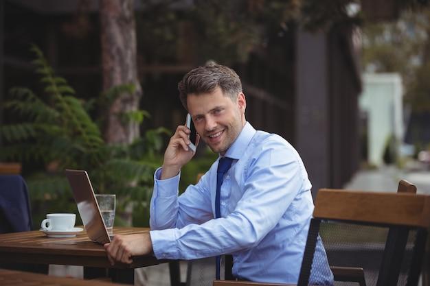 Bel homme d'affaires, parler au téléphone mobile tout en utilisant un ordinateur portable
