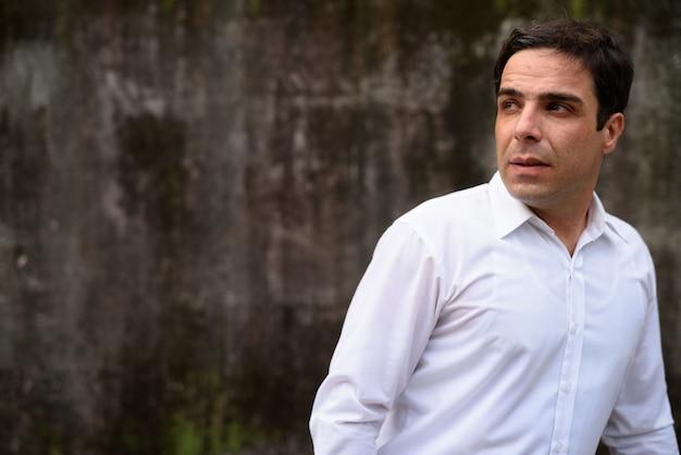 Bel homme d'affaires persan contre le mur de béton à l'extérieur