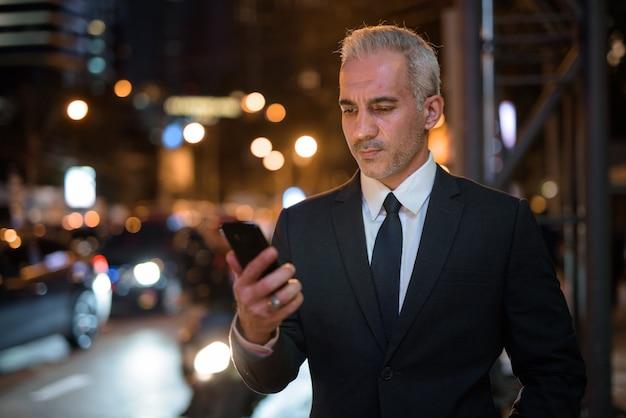 Bel homme d'affaires persan portant costume en ville pendant la nuit
