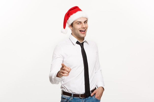 Bel homme d'affaires portant le bonnet de noel doigt pointé sur blanc.